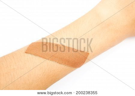 closeup of medical plaster band on arm isolated on white background