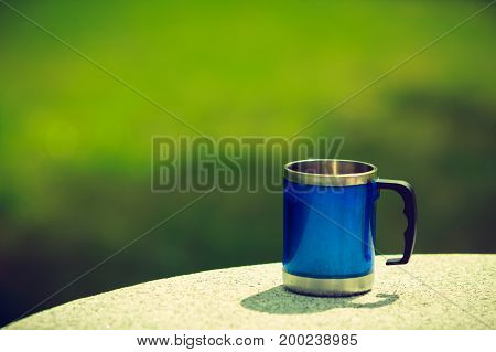 Traveling objects concept. Blue tourist cup mug outside standing on rock green scenery in background.