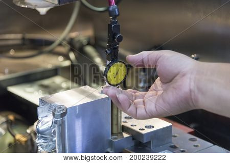 The hand of operator adjust the dial gauge.Setup the work pieces by using the dial gauge.