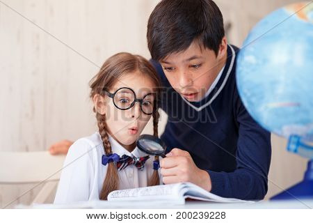 Small boy and girl staring with surprisment in book, using lens, magnifying pictures. Cute girl in eyewear wearing white shirt sitting near her classmate, looking with widely opened eyes in magnifier