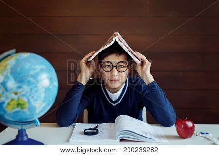 Busy schoolboy, doing his home assigment, keeping book on head, looking puzzled while not knowing how to do exercise. Boy sitting at his work place, surrounded with books and school equipment