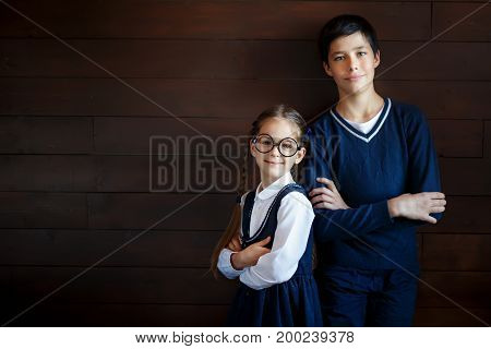 Happy schoolgirl in big spectacles and school uniform standing back to her brother. Two schoolchildren in elegant clothes, keeping their hands crossed, posing into camera while going to school