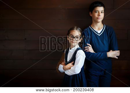 Attractive boy keeping his hands crossed while standing near his little sister in big glasses and school uniform. Positive pupils isolated over blank studio background. School, children, learning