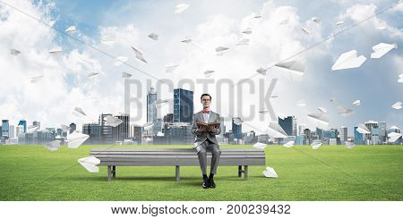 Funny man in red glasses and suit sitting on bench and reading book