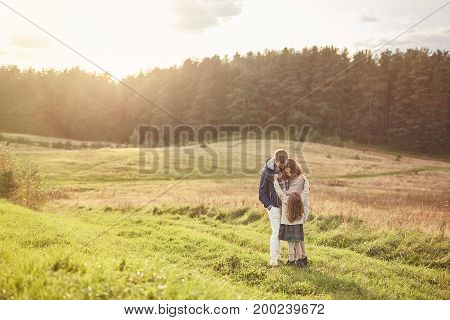Lovely family of three members standing on green grass of meadow, embracing each other while feeling support and love. Small girl standing near her careful affectionate parents. Togetherness concept