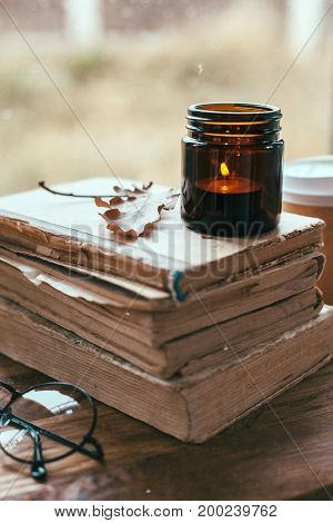 Warm and cozy scene with old book and candle on a table. Fall weekend, autumn lifestyle.