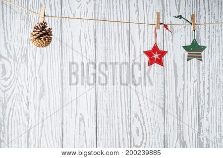 Christmas background with holiday decorations on grunge wooden board. Christmas card with red and green wooden christmas toys hanging on clothespin on white wooden wall. Xmas and New Year concept.