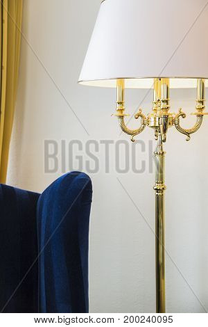 Blue velours armchair and a gold standing night-lamp in a light hotel room.