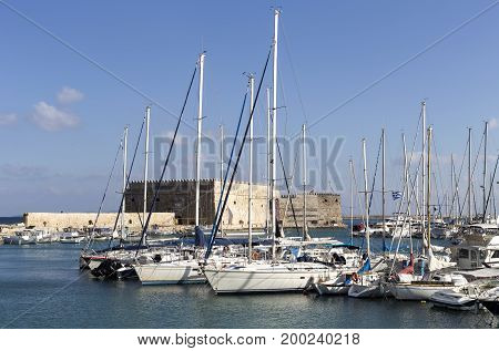 View of the quay, the Venetian fortress and the moored boats and yachts (city Heraklion, island Crete, Greece)