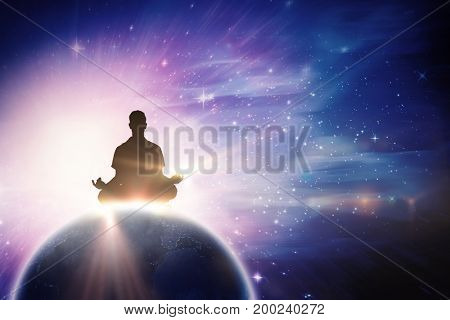 Silhouette man doing meditation against digitally composite image of colorful lights