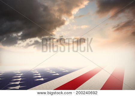 Usa national flag against blue and orange sky with clouds