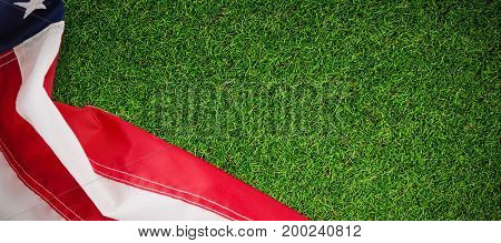 Close-up of striped American flag against close-up of grass mat