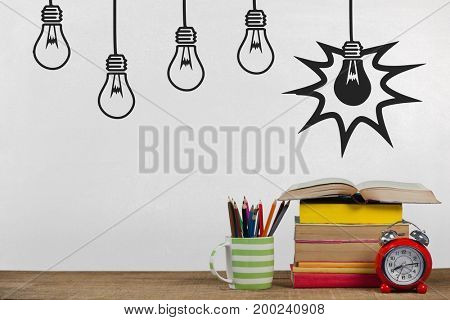 Digital composite of Books on the table against white blackboard with bulb graphics