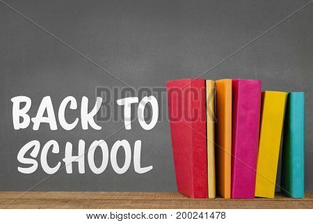 Digital composite of Books on the table against grey blackboard with back to school text