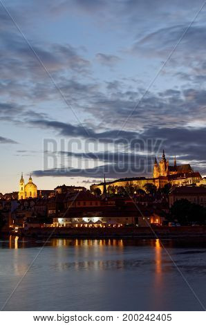 Night view on Hradcany castle.Beautifully lit castle and Vltava river in the foreground.