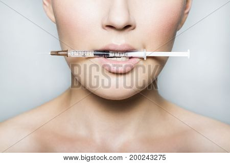 Close up portrait of a young female patient with naked shoulders holds a syringe with beauty injections in her mouth on white background