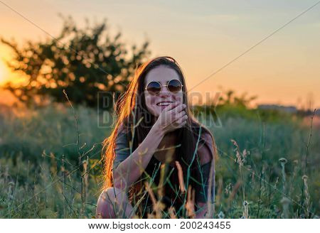 Young beautiful girl with long hair smiles in round sunglasses in the evening light sitting on grass.