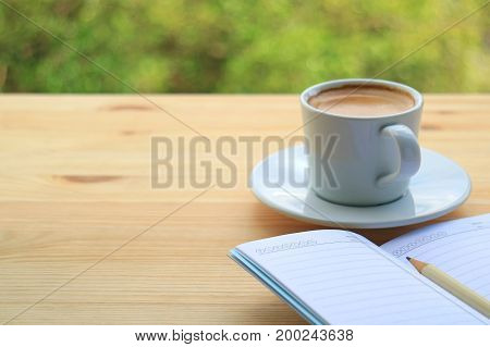 Hot Coffee with Lined Note Papers on the Wooden Table of Outdoor Seating, Blurred Green Bush in Background