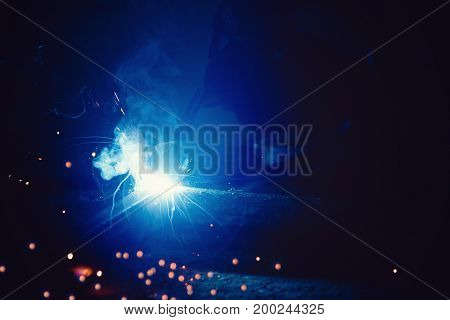 Abstract light flare from the welding machine. Flow of sparks in dark.