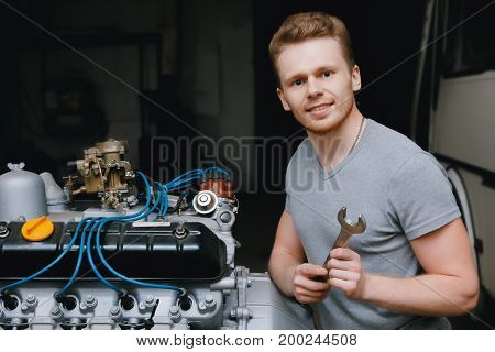 A close-up of an auto mechanic smiling repairs the engine of a lorry or bus replacement of a candle, a concept repair in a garage, a workshop.