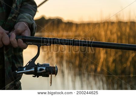 A Man Is Fishing From A Boat On Sunset. Close-up Of Hands And Rods