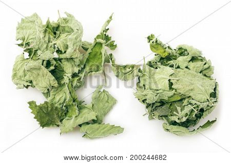 A handful of dried mint leaves on a white background. Spice
