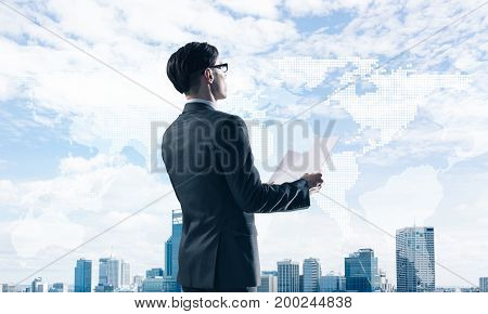 Young elegant businessman with papers in hands looking away