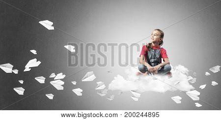 Cute kid girl sitting on cloud and paper planes flying around