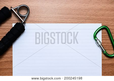 White line paper with sport equipments on brown wooden table top view