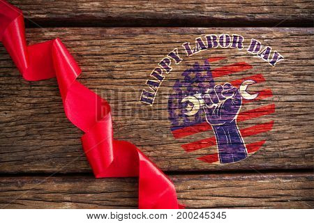 Happy labor day text over cropped hand holding tools against red ribbon on wooden table