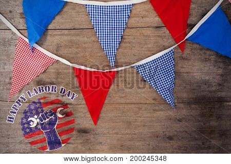 Happy labor day text over cropped hand holding tools against overhead view of buntings on wooden table