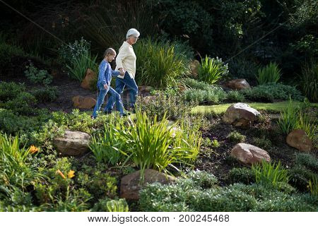 Grandmother and granddaughter walking in the garden on a sunny day