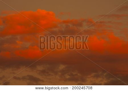Golden sky with puffy bright orange clouds creates an unusual sunset cloudscape.