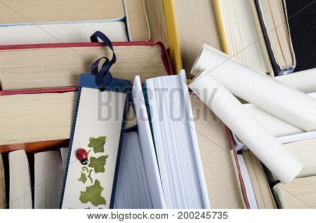 top view of a group of books and a bookmark. culture.