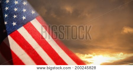 Close-up of American flag against cloudy sky landscape