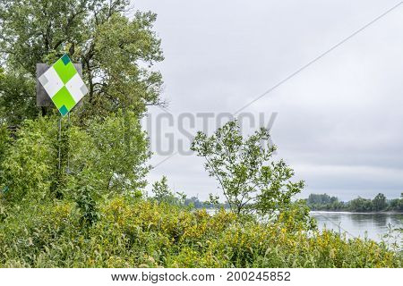 green navigational sign  on the right shore of Missouri River