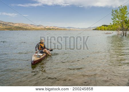 male paddler sitting on a paddleboard and putting his sandals on in preparation for landing on a mountain lake in northern Colorado, summer scenery at Horsetooth Reservoir