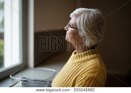 Close-up of thoughtful senior woman looking through kitchen window