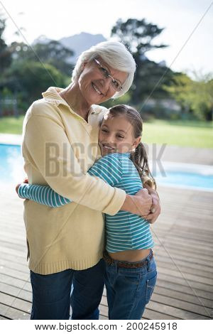 Portrait of granddaughter and grandmother embracing near the pool