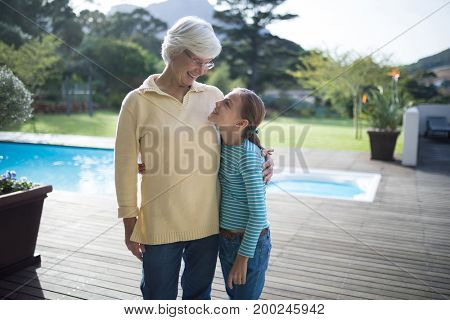Happy granddaughter and grandmother embracing near the pool