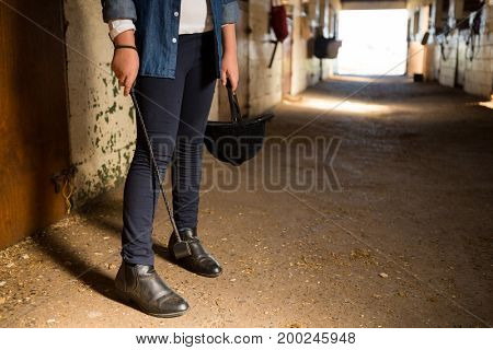 Low-section of girl standing in the stab;le