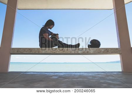 An Asian man sitting under roof next to the sea looking to his helmet