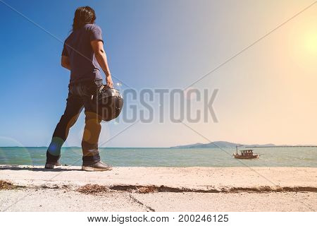 An Asian man stand turn his back next to the sea while holding his helmet and looking to the boat