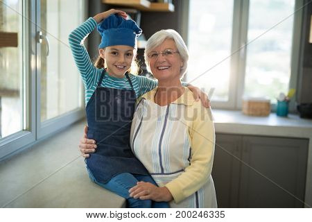 Grandmother and granddaughter posing by embracing each other in the kitchen