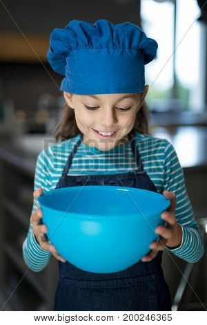 Close-up of smiling girl looking into the bowl in the kitchen