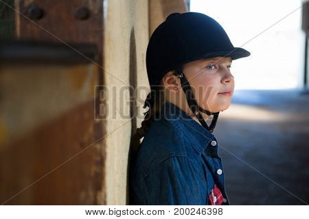 Thoughtful girl leaning on wall in the stable