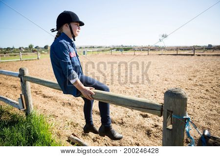 Thoughtful girl sitting on wooden fence in the ranch