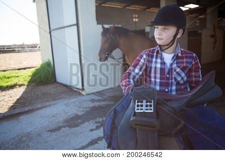 Thoughtful teenage girl holding horse equipments in the stable