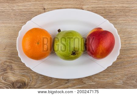 Tangerine, Pear And Nectarine In Oval Dish On Wooden Table