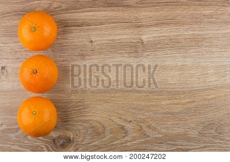 Row Of Tangerines From Left Side Of Wooden Table